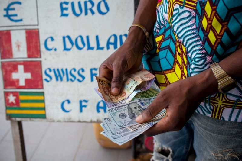 © Reuters. FILE PHOTO: A man trades U.S. dollars for Ghanaian cedis at a currency exchange office in Accra