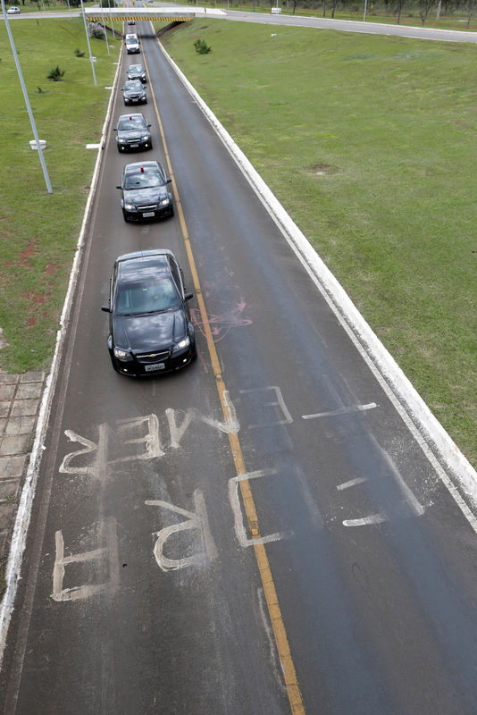 © Reuters. The motorcade of Brazilian President Michel Temer drives past graffiti which reads 'Out with Temer' in Brasilia