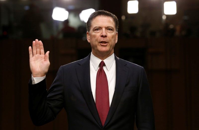 © Reuters. FILE PHOTO: Former FBI Director James Comey sworn in to testify at a hearing in Washington