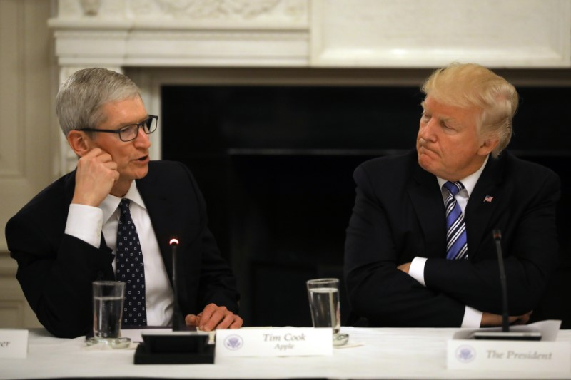 © Reuters. U.S. President Donald Trump listens as Tim Cook, CEO of Apple speaks during an American Technology Council roundtable at the White House in Washington, U.S.