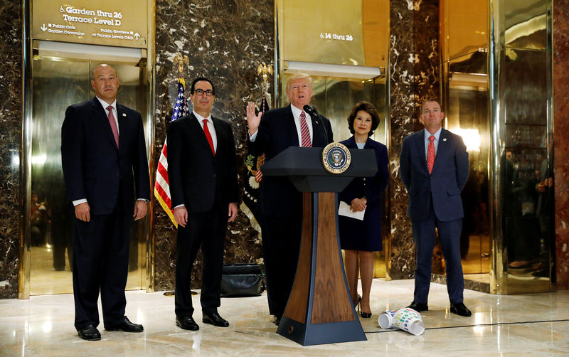 © Reuters. President Trump is flanked by staff and cabinet members as he speaks about the Charlotte violence in New York
