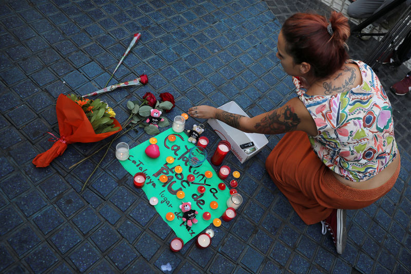 © Reuters. A woman places a candle on a placard, reading in Spanish and Catalan
