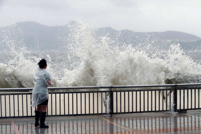 © Reuters. A woman stands beside a big wave on a waterfront Typhoon Hato hitting in Hong Kong