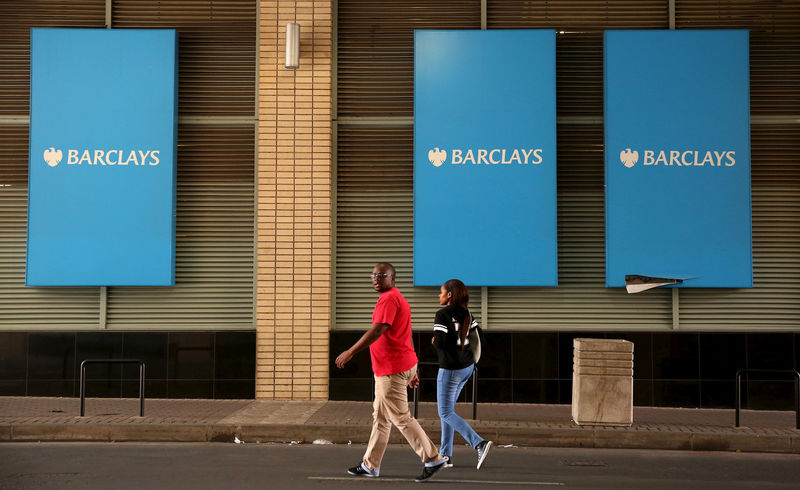 © Reuters. FILE PHOTO: A couple walks past a Barclays logo in Johannesburg
