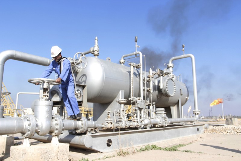 © Reuters. FILE PHOTO: A worker checks the valve of an oil pipe at Nahr Bin Umar oil field north of Basra