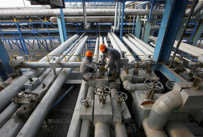 © Reuters. FILE PHOTO: Employees close a valve of a pipe at a PetroChina refinery in Lanzhou, Gansu province