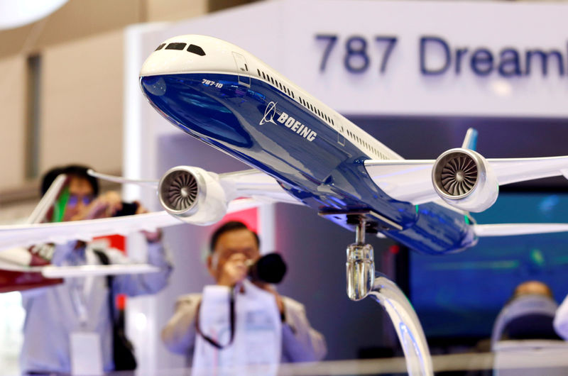 © Reuters. FILE PHOTO: Visitors take pictures of a model of Boeing's 787 Dreamliner during Japan Aerospace 2016 air show in Tokyo