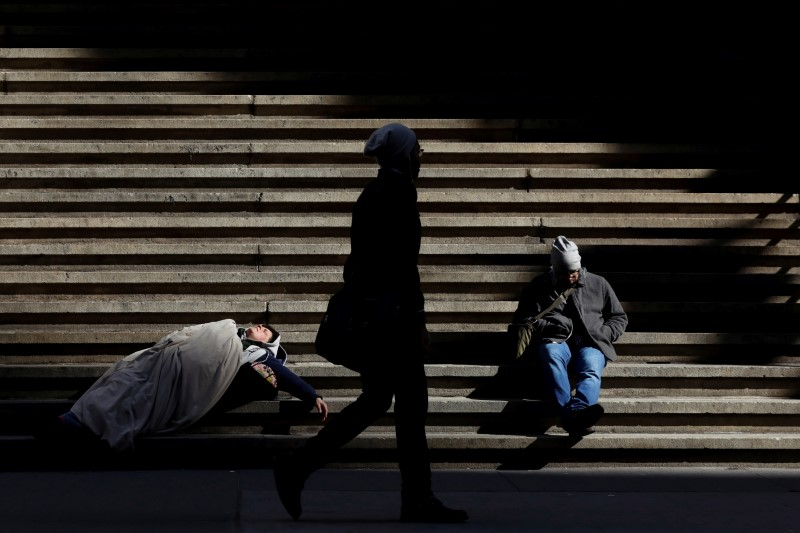 © Reuters. A homeless person sleeps on the steps of Federal Hall on Wall St. in New York City