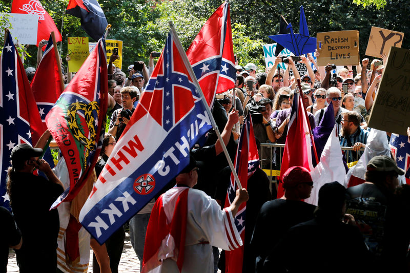 © Reuters. FILE PHOTO: Members of the Ku Klux Klan face counter-protesters as they rally in support of Confederate monuments in Charlottesville Virginia