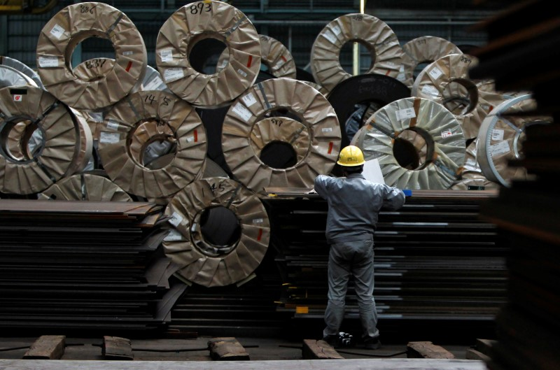 © Reuters. FILE PHOTO - A worker checks steel coils and steel sheets at a distribution warehouse in Urayasu, east of Tokyo
