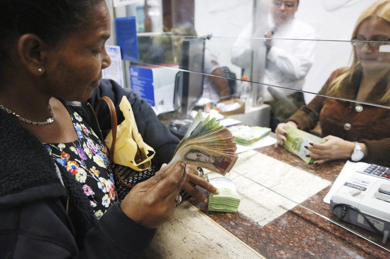 © Reuters. A woman changes dollars for bolivars at a money exchange in Caracas