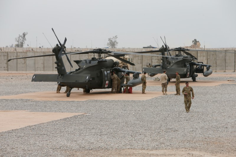 © Reuters. U.S army soldiers stand next to helicopters at the Qayyarah West Airfield