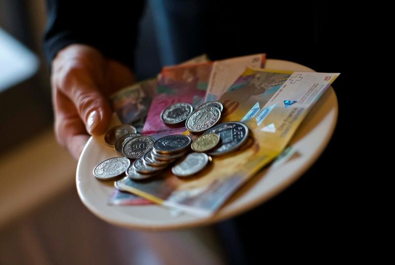 © Reuters. A waitress presents a plate with various Swiss Franc coins and notes in this picture illustration in a restaurant in Zurich