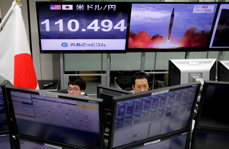 © Reuters. FILE PHOTO: Employees of a foreign exchange trading company work in front of monitors showing TV news on North Korea's threat and the Japanese yen's exchange rate against the U.S. dollar in Tokyo