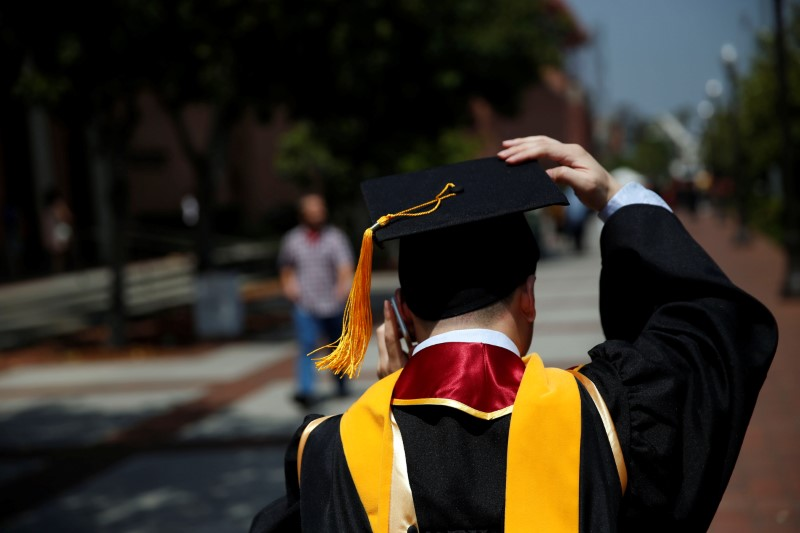 © Reuters. A graduate holds their mortarboard cap after a commencement ceremony at the University of Southern California (USC) in Los Angeles, California