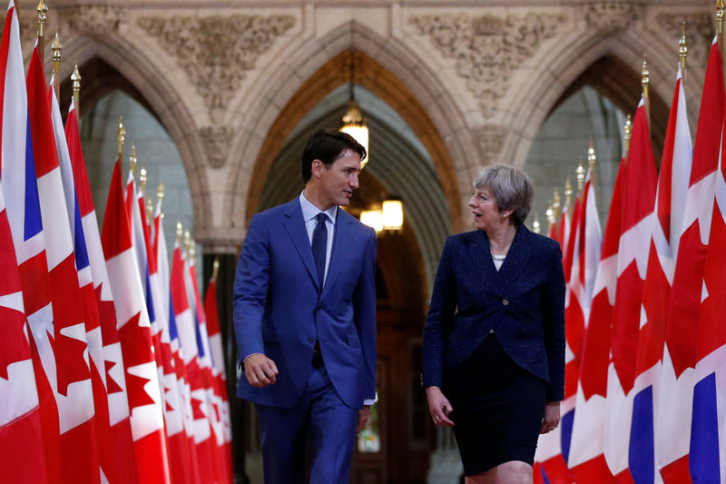 © Reuters. Canada's PM Trudeau and Britain's PM May walk in the Hall of Honour on Parliament Hill in Ottawa