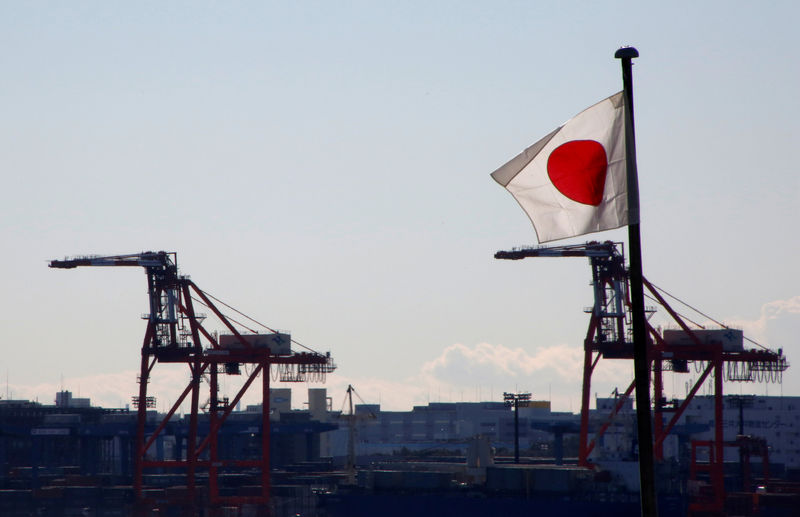 © Reuters. FILE PHOTO: Japan's national flag is seen in front of containers and cranes at an industrial port in Tokyo