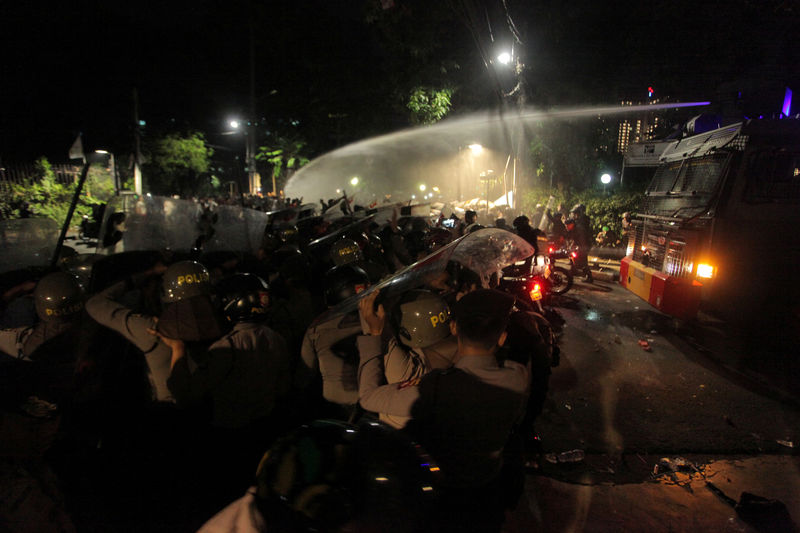 © Reuters. Police use a water cannon to disperse a crowd gathered outside the Indonesian Legal Aid Foundation during an anti-communist protest in Jakarta