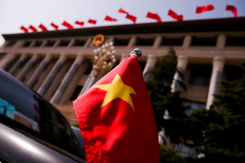 © Reuters. FILE PHOTO: The Vietnamese national flag flies on a diplomatic car outside the Great Hall of the People before talks between Vietnam's President Tran Dai Quang and Chinese leaders in Beijing