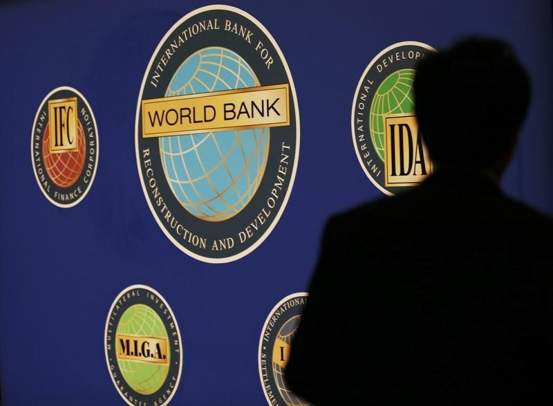 © Reuters. A man is silhouetted against the logo of the World Bank at the main venue for the IMF and World Bank annual meeting in Tokyo