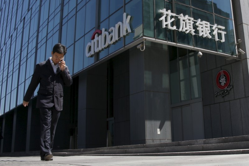 © Reuters. A man walks past a branch of Citibank in Beijing
