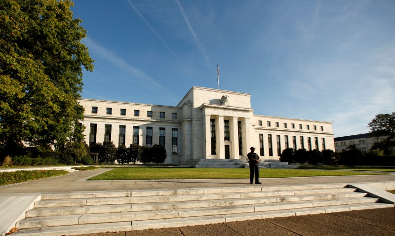 © Reuters. FILE PHOTO: A police officer keeps watch in front of the U.S. Federal Reserve in Washington