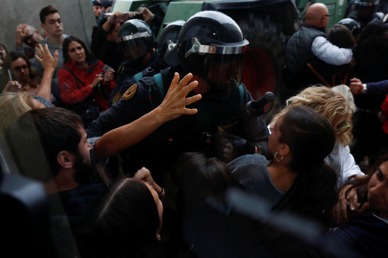 © Reuters. Scuffles break out as Spanish Civil Guard officers force their way through a crowd and into a polling station for the banned independence referendum in Sant Julia de Ramis
