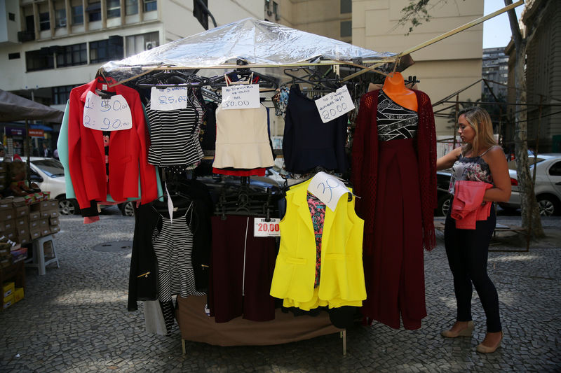 © Reuters. FILE PHOTO: A woman looks on clothes for sale at a street market in Rio de Janeiro