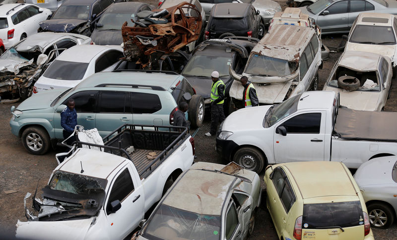 © Reuters. Dealers inspect vehicles before their auction at the Leakey's auctioneers yard in Nairobi