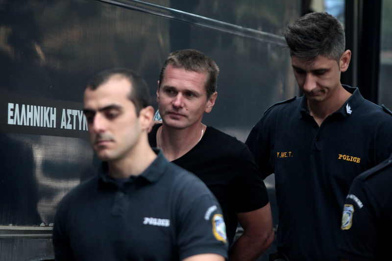© Reuters. Alexander Vinnik, a 38 year old Russian man suspected of running a money laundering operation using bitcoin, is escorted by police officers to a court in Thessalonik