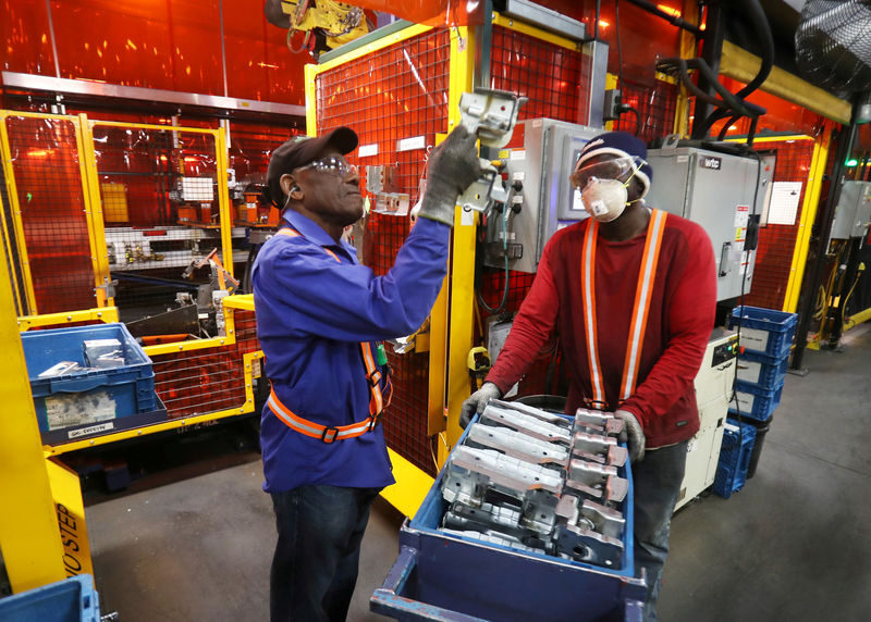 © Reuters. FILE PHOTO:    Workers examine parts for welding next to robot bay at Alfield Industries.