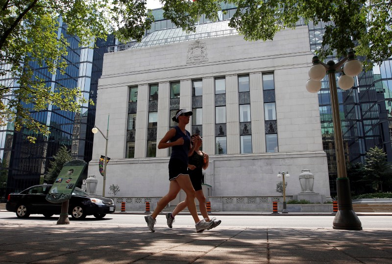 © Reuters. FILE PHOTO: Joggers run past the Bank of Canada building in Ottawa