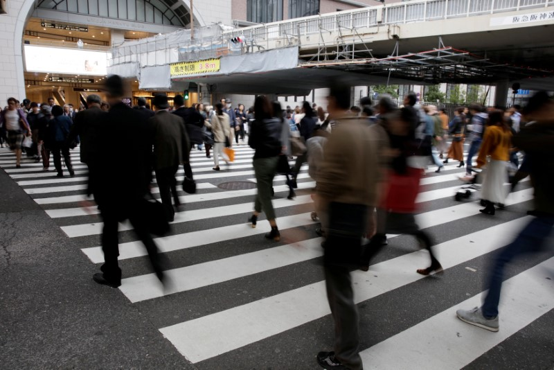 © Reuters. FILE PHOTO: Commuters cross a pedestrian crossing in Osaka