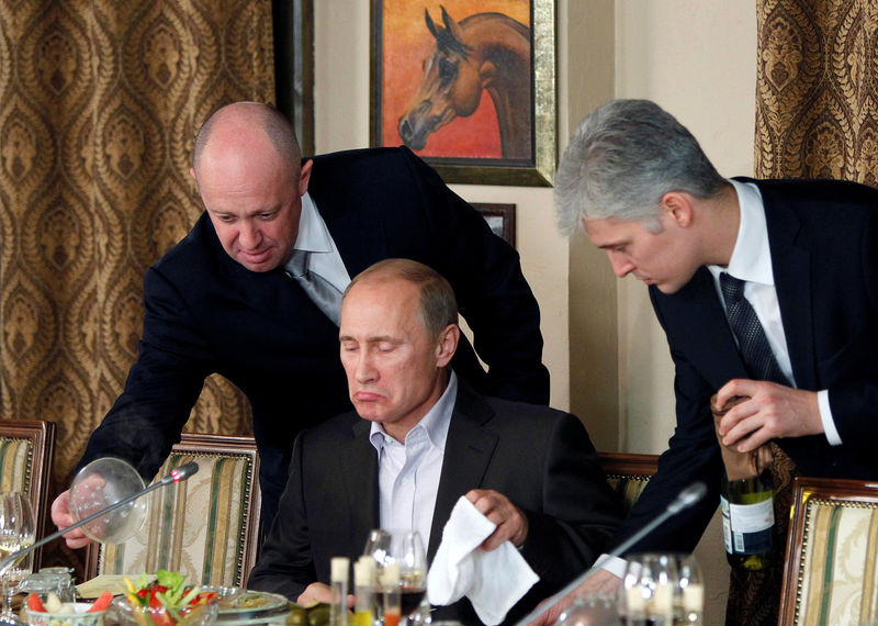 © Reuters. FILE PHOTO:    Evgeny Prigozhin assists Russian Prime Minister Vladimir Putin during a dinner with foreign scholars and journalists at the restaurant Cheval Blanc on the premises of an equestrian complex outside Moscow