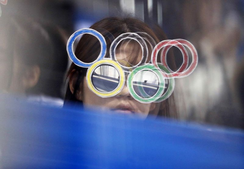 © Reuters. A fan wearing Olympic rings glasses watches a hockey game in Pyeongchang