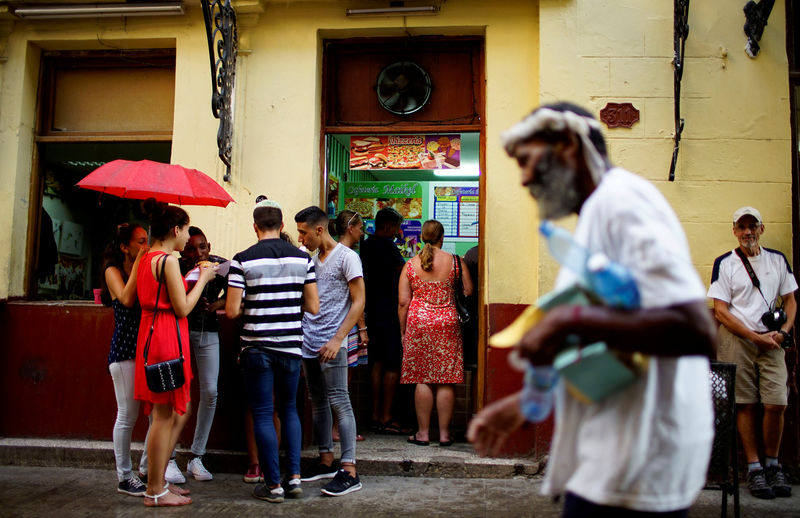 © Reuters. FILE PHOTO: People stand in front of a private restaurant in Havana, Cuba