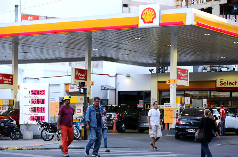 © Reuters. People walk in front of a Shell gas station in Buenos Aires