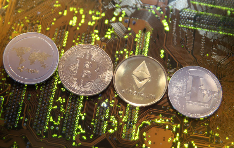 © Reuters. Representations of the Ripple, Bitcoin, Etherum and Litecoin virtual currencies are seen on motherboard in this illustration picture