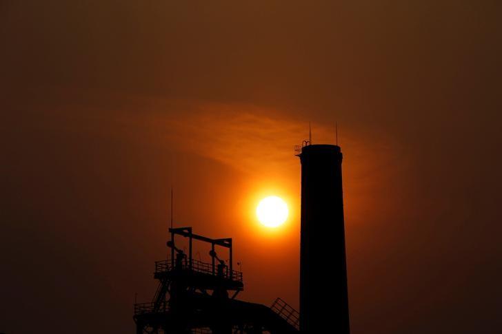 © Reuters. Por do sol atrás de chaminé de usina de aço em Tangshan