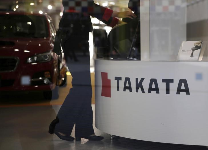 © Reuters. FILE PHOTO: A woman stands next to a logo of Takata Corp at a showroom for vehicles in Tokyo