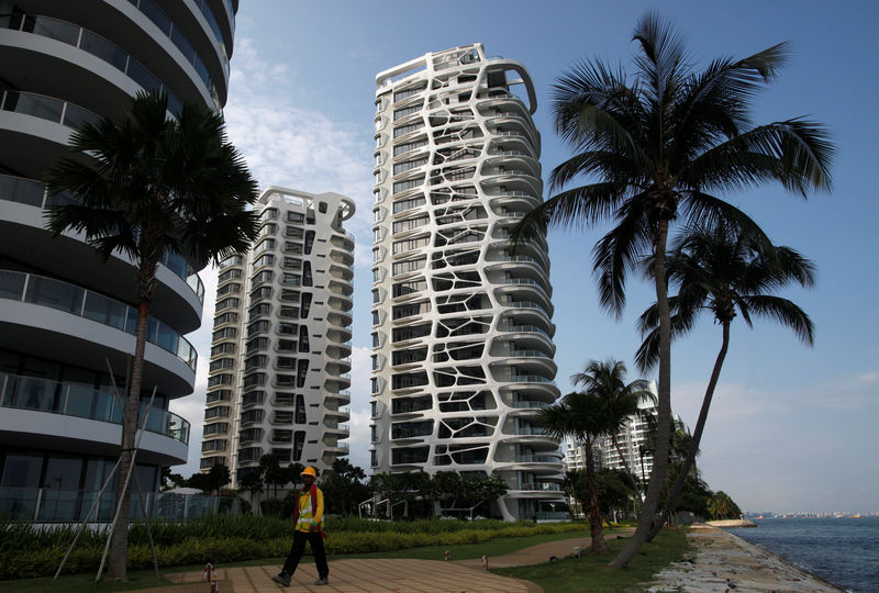 © Reuters. FILE PHOTO: A construction worker passes the largely vacant Cape Royale condominium in Sentosa Cove on Singapore's Sentosa island