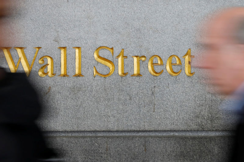 © Reuters. People walk by a Wall Street sign close to the NYSE in New York