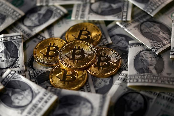 © Reuters. Монеты биткоина и долларовые купюры