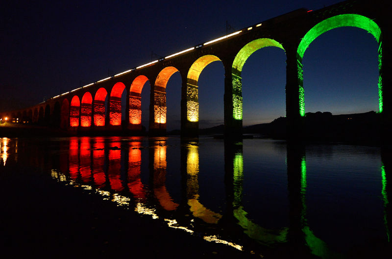 © Reuters. FILE PHOTO: A train travelling on the East Coast mainline is reflected in the River Tweed as it crosses the Royal Border Bridge at dusk, in Berwick-Upon-Tweed in Northumberland