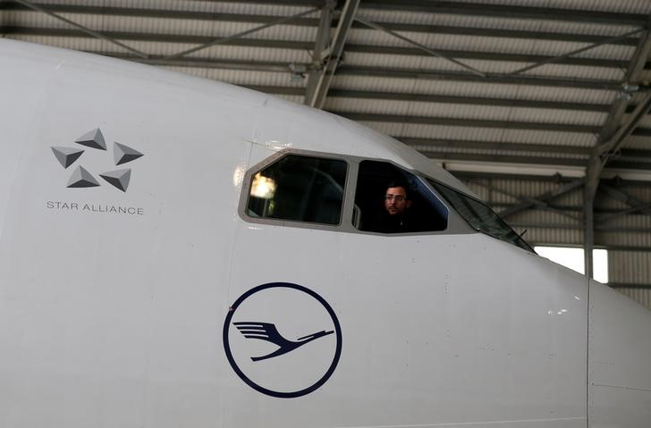 © Reuters. A technician looks out of the cockpit of a Lufthansa Airbus A330-300 aircraft in a maintenance hangar at Lufthansa Technik Malta at Malta International Airport outside Luqa
