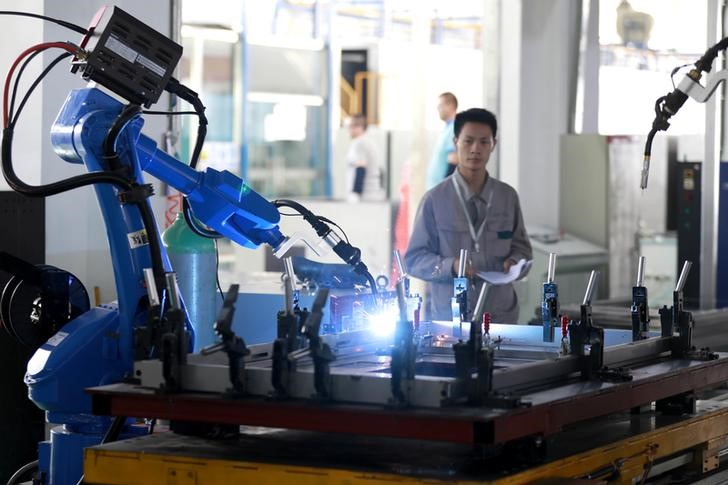 © Reuters. FILE PHOTO: Worker monitors a robotic arm working inside a factory in Huaian