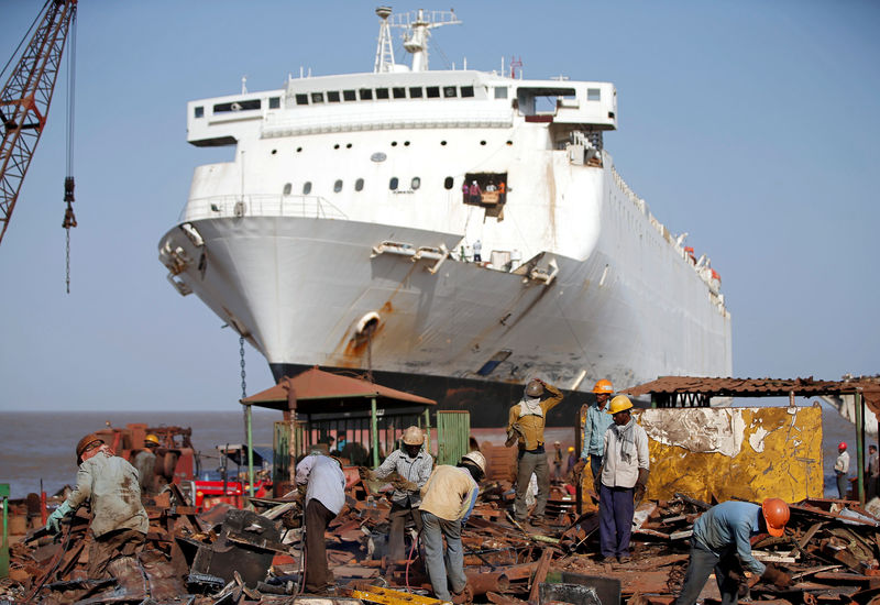 © Reuters. FILE PHOTO: Workers sort out scrap metal of a decommissioned ship at the Alang shipyard