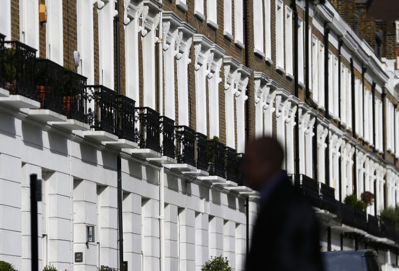 © Reuters. A man walks past a row of houses in Chelsea in London