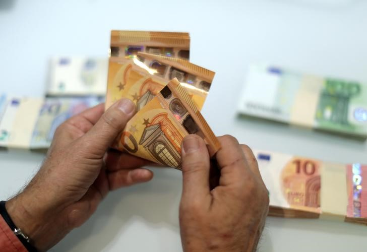 © Reuters. FILE PHOTO: A money changer counts Euro banknotes at a currency exchange office in Nice