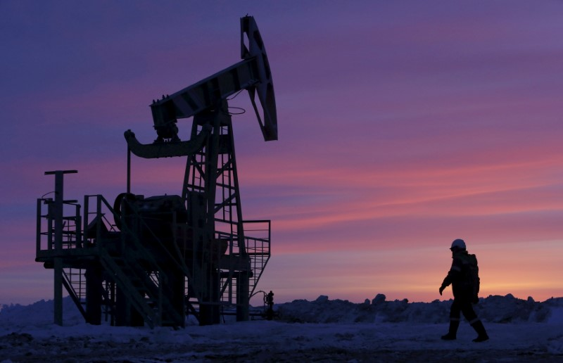 © Reuters. FILE PHOTO: File photo of a worker walking past a pump jack on an oil field owned by Bashneft, Bashkortostan